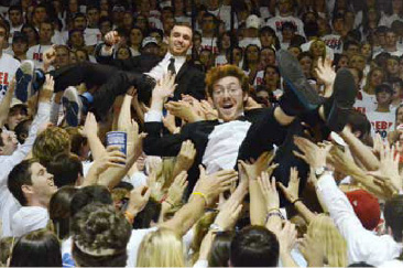 """Blake Pruett and Patrick Haadsma, known as King Kobraz, crowd surf while shooting the video for their new song """"TSUNs of Guns"""" before the basketball game against Kentucky. Photo by Phillip Waller for the Daily Mississippian"""