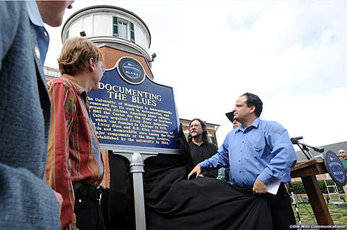 "Mark Camarigg, publications manager of Living Blues magazine, Jim O'Neal, co-founder of LB, Brett Bonner, LB editor, and Scott Barretta, Highway 61 Radio host unveil the Blues Marker honoring ""Living Blues"" magazine which is published at The University of Mississippi."