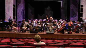 Nancy Van de Vate listens to the cast and orchestra during the sitzprobe, or seated rehearsal, in the Ford Center.