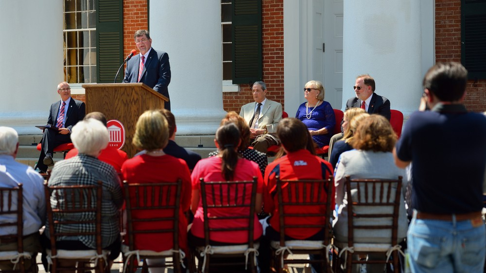 Morris Stocks (standing), acting chancellor at the University of Mississippi, announces that the Gertrude C. Ford Foundation has agreed to increase its support for the university's new science building during a Friday (Sept. 4) event on the steps of the Lyceum. Also participating the announcement are Acting Provost Noel Wilkin (left) and Ford Foundation board members Anthony Papa, Cheryle Sims and John Lewis. Photo by Robert Jordan/Ole Miss Communications