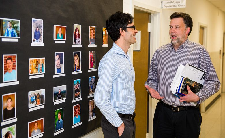 Department of History Chair Joseph P. Ward, right, chats with Zachary Kagan Guthrie, assistant professor of history, near a wall showcasing the department's graduate students. The Brig. Gen. John H. Napier III Endowment will support research efforts of the Arch Dalrymple III Department of History faculty and doctoral students.