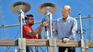 UM physicists Sampath Bandara (left) and Thomas Marshall place a light sensor in place as part of their study of lightning strikes. | Photo by Robert Jordan, UM Communications
