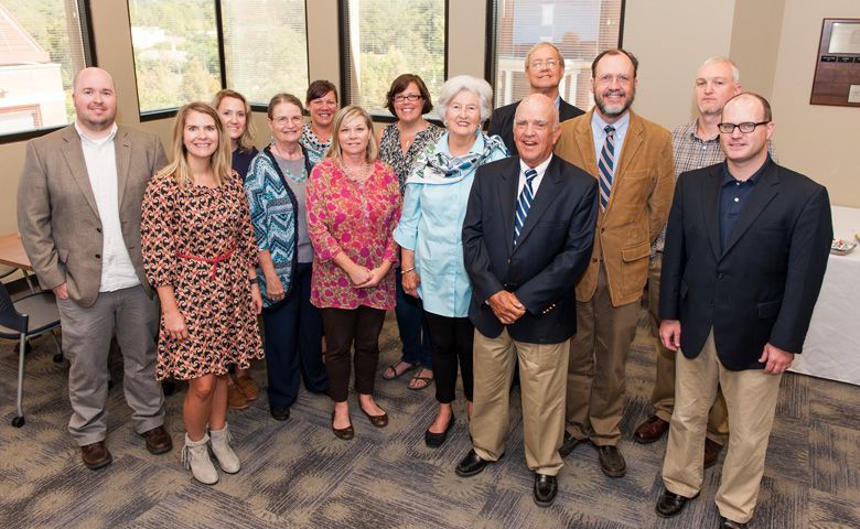 Reba Greer (center, in blue) and her husband Lance (to her left) attend a reception in their honor hosted by faculty and staff of the Department of Writing and Rhetoric for which the Greers established an endowment.