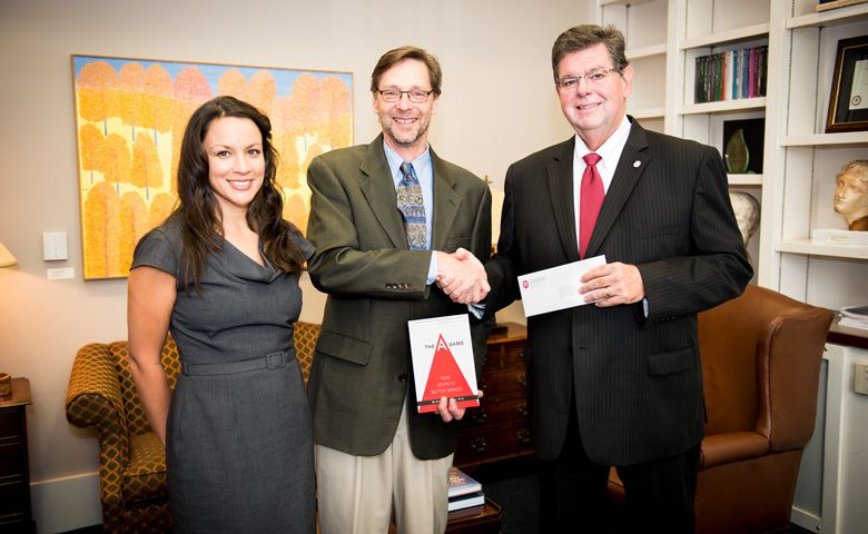 Ken Sufka (center), UM professor of psychology and pharmacology, and wife, Stevi, have established a scholarship from royalties received from the publication of Sufka's book. UM Provost Morris Stocks (right) was instrumental in making the book required reading for all entering students.