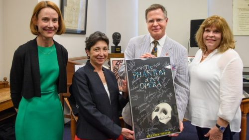 Jennifer Ford (left), head of the Department of Archives and Special Collections, and Cecilia Botero, UM dean of libraries, share an autographed poster from 'The Phantom of the Opera' with Chancellor Jeffrey Vitter and his wife, Sharon. The poster is a gift from the Actors Fund of America. Photo by Robert Jordan/Ole Miss Communications