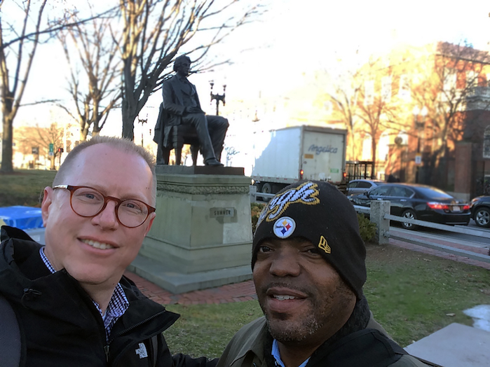 """Jeff Jackson (left) and Chuck Ross (right) posing with the statue of abolitionist Senator Charles Sumner while in Cambridge, Massachusetts, for the """"Universities and Slavery: Bound by History"""" conference at the Radcliffe Institute for Advanced Study at Harvard University. Photo by Jeffrey Jackson, March 2017."""
