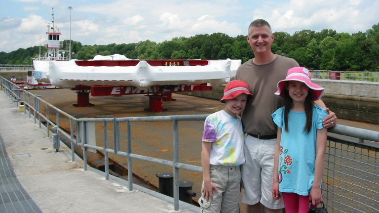 Breese Quinn and his son, Aidan, and daughter, Erin, watch the Muon g-2 ring pass through the G.V. 'Sonny' Montgomery Lock on the Tennessee-Tombigbee Waterway on July 15, 2013. Quinn is among the collaborators on a landmark experiment using the massive electromagnet at Fermilab. Photo courtesy Breese Quinn