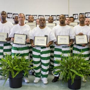 Co-directors Otis Pickett (back row, left) and Patrick Alexander (back row, right) with 16 graduates of the summer 2016 Prison-to-College Pipeline course at the Mississippi State Penitentiary. Submitted photo/Mississippi Department of Corrections