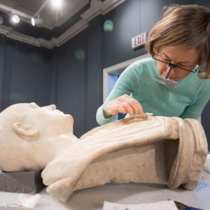 Conservator Amy Jones Abbe gives the Bust of an Unknown Roman a careful cleaning as part of her residency at University Museum. Photo by Kevin Bain/Ole Miss Communications