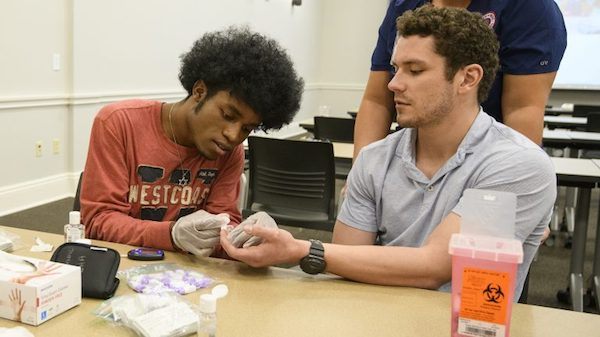 Micah Walls (left) and Conner Ball practice taking each other's blood glucose levels. Photo by Thomas Graning/Ole Miss Communications