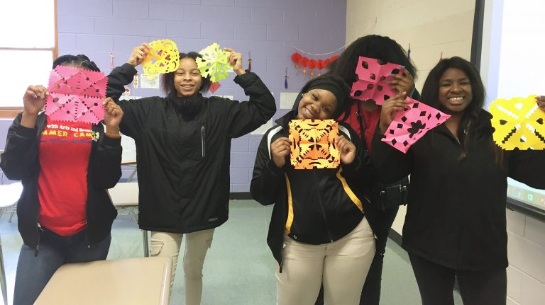 Victoria Nabors (left), T'khya Williams, Kelvisha Conner, Fredrekia Campbell and Kennytra Martin, all Chinese 1 students at Holly Spring High School, show off their Asian-themed paper cuttings at the school. UM photo by Linfei Yi