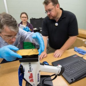 Brad Cook, UM associate professor of classics, balances an ancient Greek inscription over an X-ray fluorescent spectrometer as Lance Yarbrough, assistant professor of geology and geological engineering, and Melanie Munns Antonelli, collections manager for the University Museum, watch. Photo by Kevin Bain