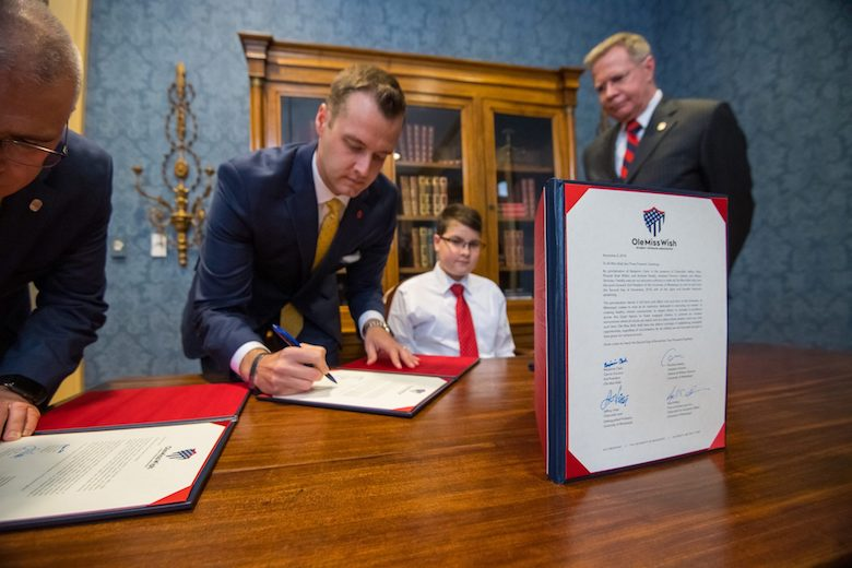 Andrew Newby (left center), assistant director for Veteran and Military Services, signs a proclamation declaring Ole Miss Wish Kid Benjamin Clark as 'Kid President' of the University of Mississippi on Friday (Nov. 2) as Chancellor Jeffrey Vitter looks on at the Lyceum. The proclamation states that all future Ole Miss Wish recipients will also serve as 'Kid President.' Photo by Kevin Bain