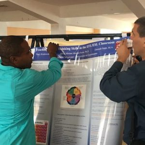 Cuba TIES IV Conference participants help set up one of the posters by UM faculty for presentation.