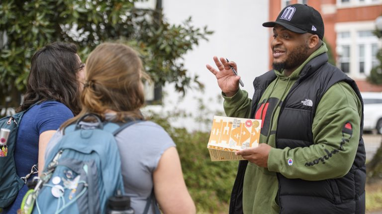 Kiese Laymon autographs a copy of his book 'Heavy: An American Memoir' for fans outside the Lafayette County Courthouse. Laymon was a featured speaker in the 2019 Conference for the Book. Photo by Thomas Graning