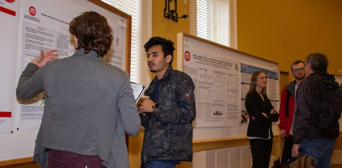 Participants in the UM Neuroscience Research Showcase poster competition examine and discuss their presentations.
