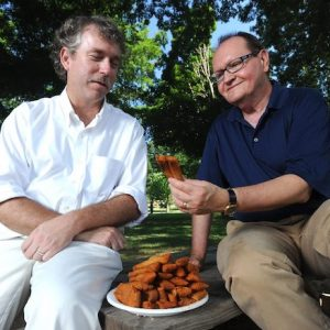 Ted Ownby (left) and Charles Reagan Wilson, discuss Southern culture while enjoying some tamales in the Grove at the University of Mississippi. Both men previously served as director at the university's Center for the Study of Southern Culture. Photo by Kevin Bain