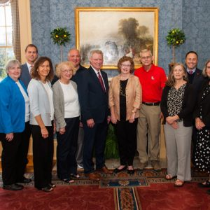 Dr. Rhett Atkinson (in red) and his wife Elaine (center) established the Doctors Andrew Stefani and Eldon Miller Memorial Chair for STEM Teaching and Research Endowment. Pictured with the Atkinsons are members of the Stefani and Miller families and UM administrators. They are (from left) Roger and Mary Jane Thornton (JoAnn Stefani's sister and brother-in-law); Denson Hollis, executive director of development; Anne Stefani (Dr. Stefani's daughter); JoAnn Stefani (Dr. Stefani's wife); Patrick Booth (Anne Stefani's husband); UM Chancellor Glenn Boyce; the Atkinsons; Tonya Dalton (Dr. Miller's daughter); Lee Cohen, dean of the College of Liberal Arts; Christine Reiner (JoAnn Stefani's sister); and Charles Hussey, associate dean for research and graduate education/professor of chemistry and biochemistry.