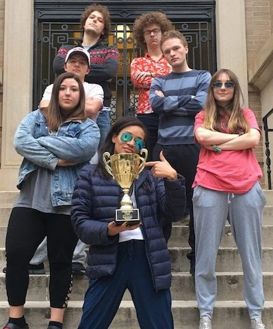 UM Ethics Bowl team members celebrate winning the Mid-Atlantic Regional Championship. Bria Mazique (front) shows off the team's trophy with (clockwise) Alexandra Kotter, John Jacob Mabus, Justice Strickland, Jacob Ratliff, Harrison Durland and Mimi Shufelt.