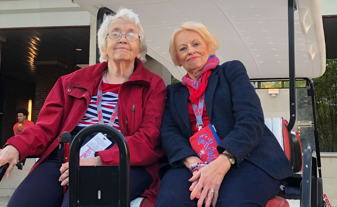 Millie Craig (left) and Barbara Beckmann enjoy a golf-cart tour of campus during the 2019 Texas A&M football weekend.