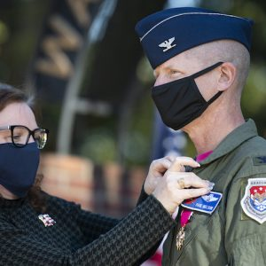 Betsy Nelson pins an Air Force retirement pin to her husband's flight suit. Col. Paul 'Voodoo' Nelson held his retirement ceremony at the Walk of Champions, the same place he was commissioned more than three decades earlier. Photo by Logan Kirkland/Ole Miss Digital Imaging Services