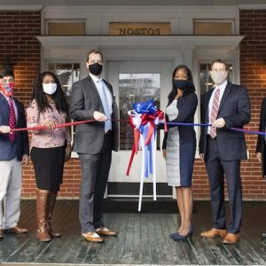 Andrew Newby (center left), assistant director for the Office of Veteran and Military Services, and Natasha Jeter (center right), vice chancellor for student affairs, cut the ribbon to the newly renovated VMS offices in George Street House. They are joined by (from left) Perry Sansing, Jamie King, Will Mobley, Stelenna Lloyd, Kyle Ellis, Provost Noel Wilkin and Cathy Baker. Photo by Logan Kirkland/Ole Miss Digital Imaging Services
