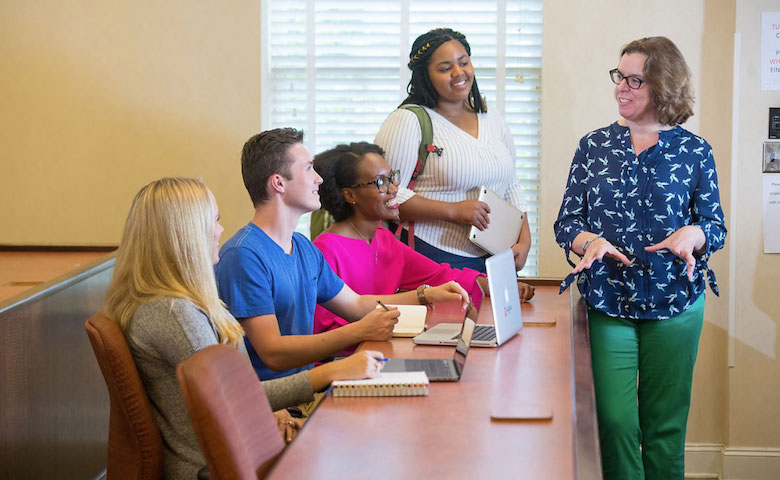 Pictured in 2019, Melissa Bass (right), associate professor of public policy leadership, instructs Lott Institute students (from left) Katherine Sistrunk, Tristin Young, Kynnedi Taylor-Henry and Yasmine Brown. Below: Members of the Green family are (from left) Mary Bea, John, Kate, Jack and Henry.