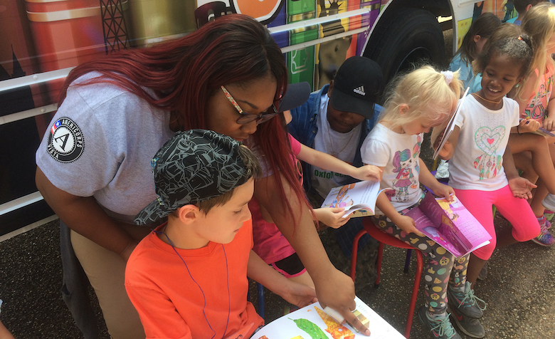 UM social work graduate Armonti Johnson (left) helps children pick out books and read at the LOU mobile library. The New Albany native is a member of the Americorps VISTA program and has served organizations throughout north Mississippi. Submitted photo