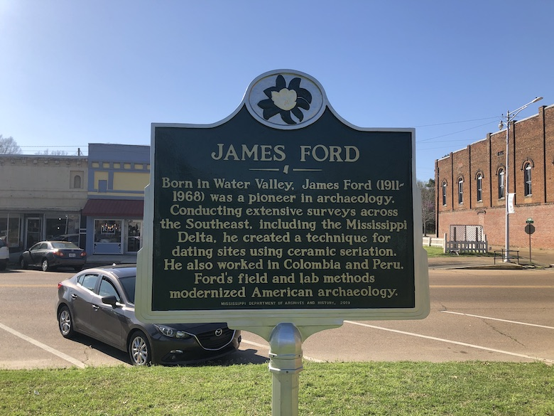 """James Ford historical marker in Water Valley, Mississippi. The marker reads: """"Conducting extensive surveys across the Southeast, including the Mississippi Delta, he created a technique for dating sites using ceramic seriation. He also worked in Columbia and Peru. Ford's field and lab methods modernized American archaeology."""""""