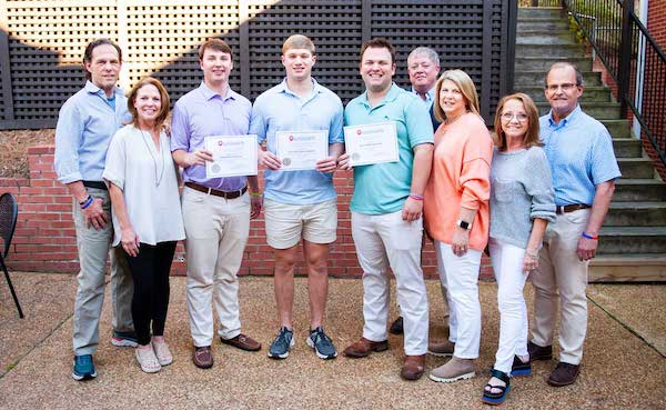 Kappa Alpha fraternity brothers (with certificates, from left) Andrew Cofield, Peyton Greenwood and Westbrooks Ross, recipients of the 2021 Kelly Kelly & Wilbanks Scholarship, are joined by (from left) Ken and Lynn Wilbanks, Chris and Christine Kelly, and Kim and Sam Kelly.