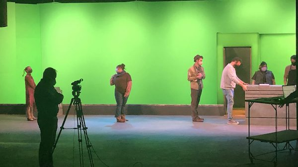 Cast members for the production of 'Urinetown' rehearse before a green screen in Meek Hall Auditorium. Submitted photo