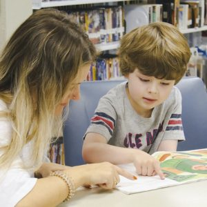 Ole Miss student Jodie Bartlett (left), of Bay St. Louis, teaches reading to rising first-grader Jackson Knight, of Oxford. Photo by Mary Stanton Knight/University Development