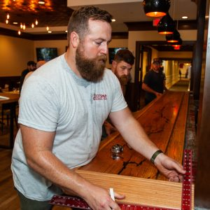 UM alumnus Ben Napier helps install a bar top he created at McCormick's, the new full-service restaurant and bar at The Inn at Ole Miss. Photo by Bill Dabney/UM Foundation