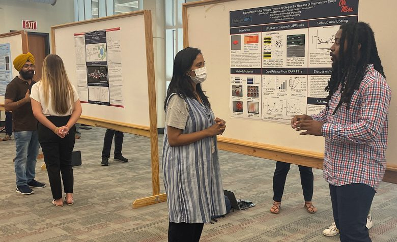 Jared Barnes (right), a senior biology major from Grenada, talks about his biodegradable drug delivery system research during a poster presentation for the UM Summer Undergraduate Research Group Grant program. Photo by Shea Stewart/UM Office of Research and Sponsored Programs