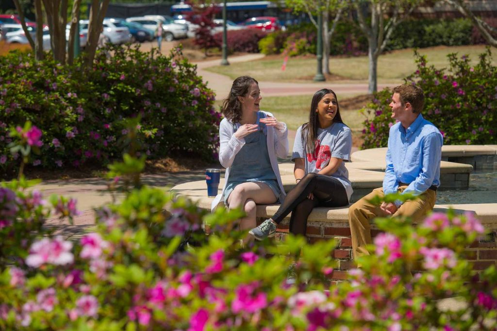 College of Liberal Arts students Sophia Fosdick, left, Cayla Hari and Weston Liefer chat at the Phi Mu fountain in the Quad.  Photo by Kevin Bain/University Communications Photography.