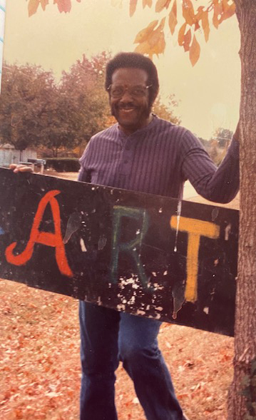 """M.B. Mayfield smiles with a sign that says """"art"""""""